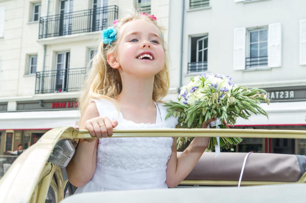 Petite fille d'honneur, fleurs dans les cheveux et bouquet à la main