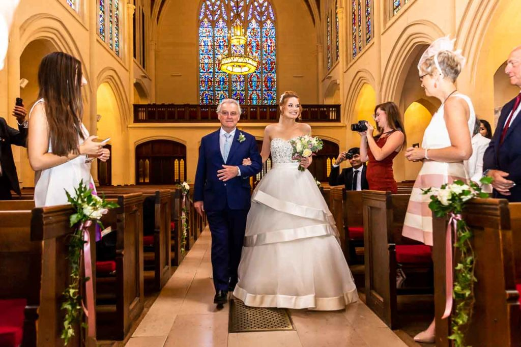 Le bouquet de la mariée en harmonie avec les fleurs à l'Eglise, sur les boutonnières des Papas et des garçons d'honneur