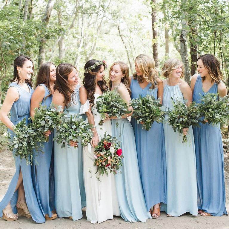 Demoiselles d'honneur qui enlacent la mariée , en robe bleu foncé et bleu ciel