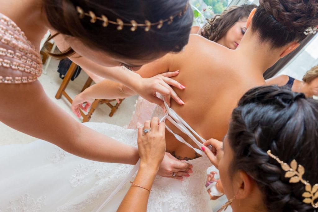 Les Préparatifs de la mariée : les demoiselles fixent la robe de mariée