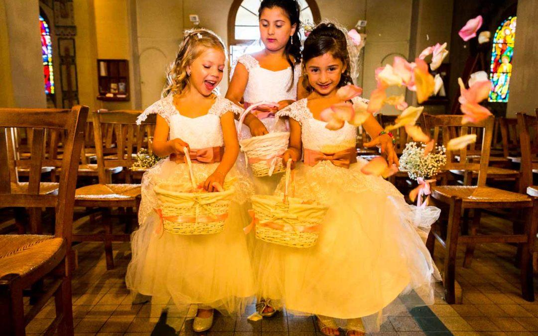 Les petites filles d'honneur lancent des pétales de roses sur l'allée de la future mariée