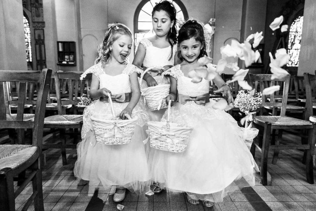 L'entrée dans l'église des petites filles d'honneur qui lancent des pétales de roses Crédits : Les Photos de Bela